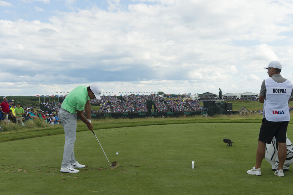 Ricky Elliott looks on as Brooks Koepka hits his tee shot on the ninth hole during the final round of the 2017 U.S. Open at Erin Hills in Erin, Wis. on Sunday, June 18, 2017. (Copyright USGA/JD Cuban)
