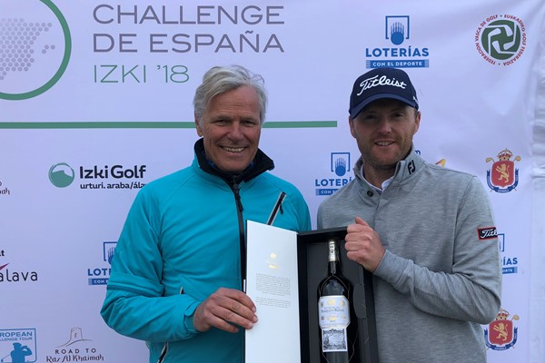 Michael Hoey is presented with a bottle of Spanish red wine, courtesy of hole-in-one sponsor Herederos del Marques de Riscal, by Challenge Tour director Alain de Soultrait in celebration of his ace.