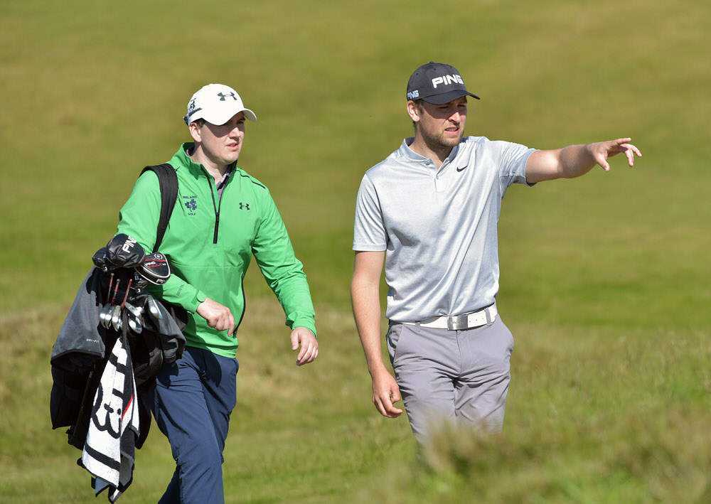 Jonathan Yates (Naas) with International teammate Colm Campbell helping on the bag during his recovery from injury at the Flogas Irish Amateur Open Championship at Royal County Down Golf. Picture by  Pat Cashman