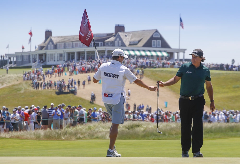 Phil Mickelson gives his putter to his brother/caddie Tim Mickelson on the first green during the third round of the 2018 U.S. Open at Shinnecock Hills Golf Club in Southampton, N.Y. on Saturday, June 16, 2018.  (Copyright USGA/Jeff Haynes)