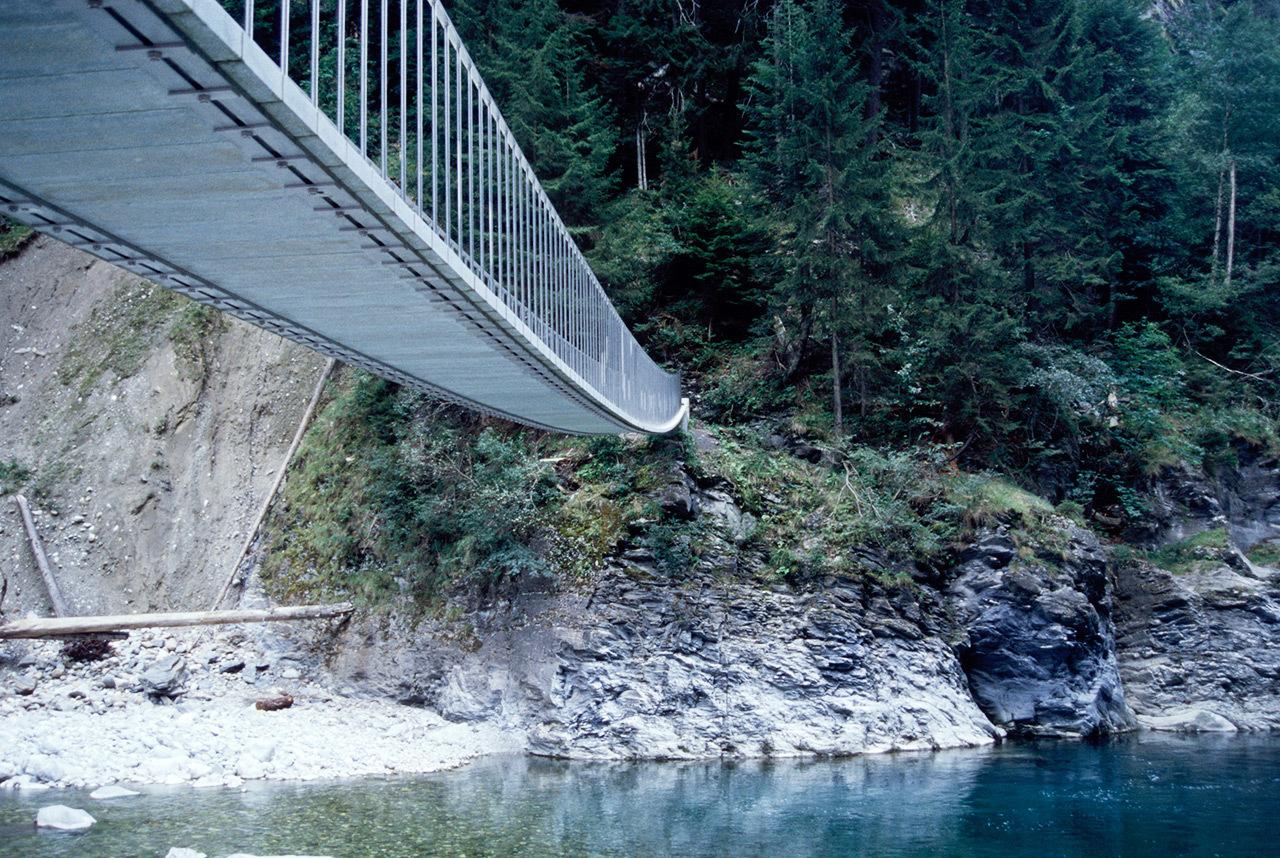 Pùnt da Suransuns Viamala, Graubunden, Switzerland. 1997 - 1999. The engineer Jürg Conzett designed this elegant footbridge, it spans 40 meters over a glaciar blue stream. It is made of granite stone slabs that hang from steel bands.