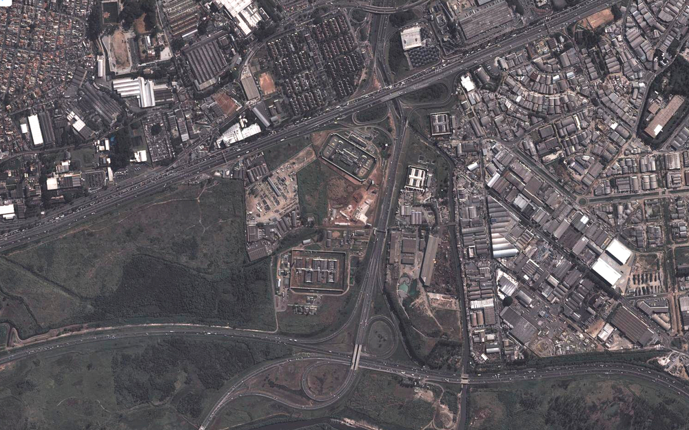 Aerial view of a complex of four prisons set in-between highway interchanges in the periphery of the city.