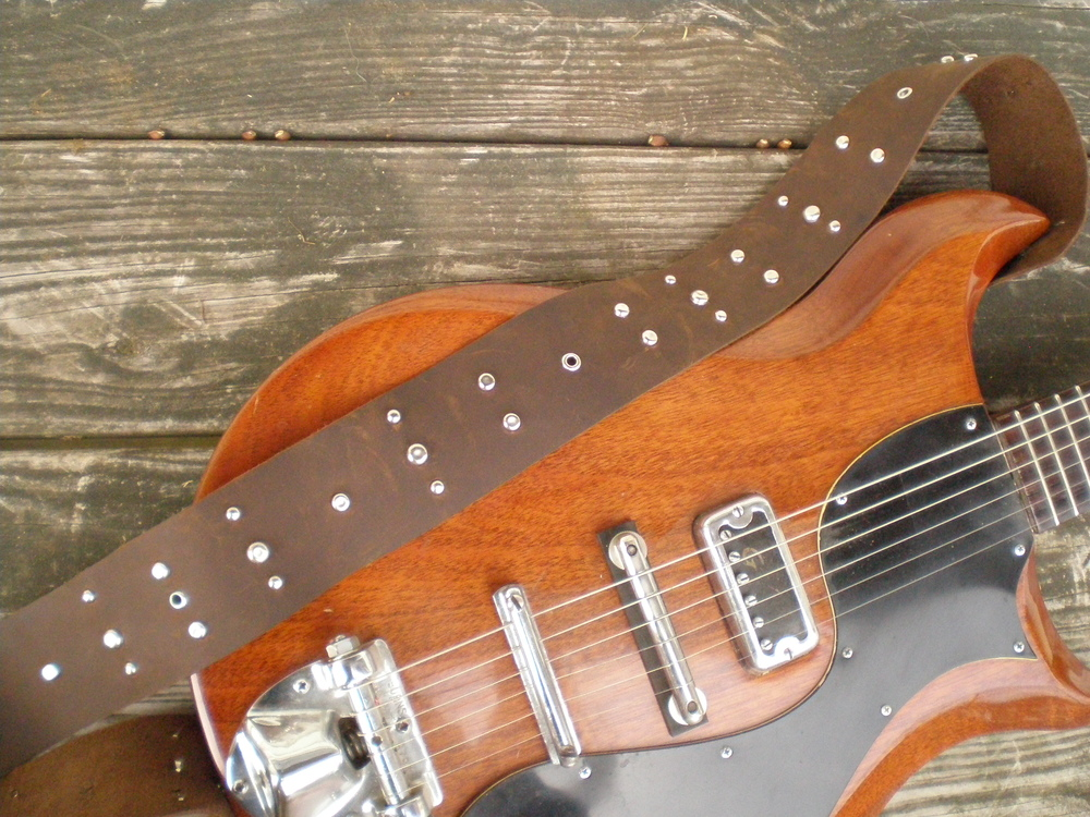 Studded Leather Guitar Strap  : Thick brown leather littered with steel studs. I have a handful of different types of studs...the metal kind ;)
