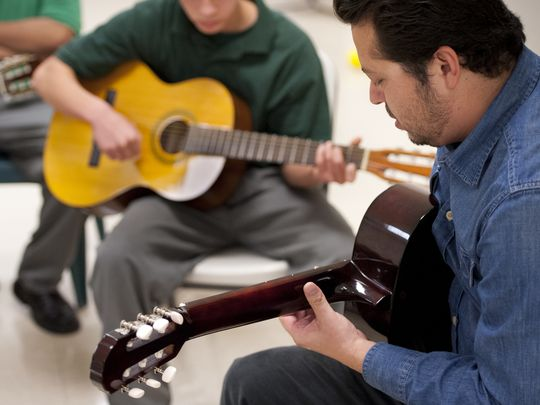 Carlos Rodriguez of Mezcal teaches guitar to youth at Tulare County Probation Youth Facility on Monday, December 14, 2015. Students must behave in and out of all classes to participate in the extracurricular activity.     (Photo: Ron Holman)