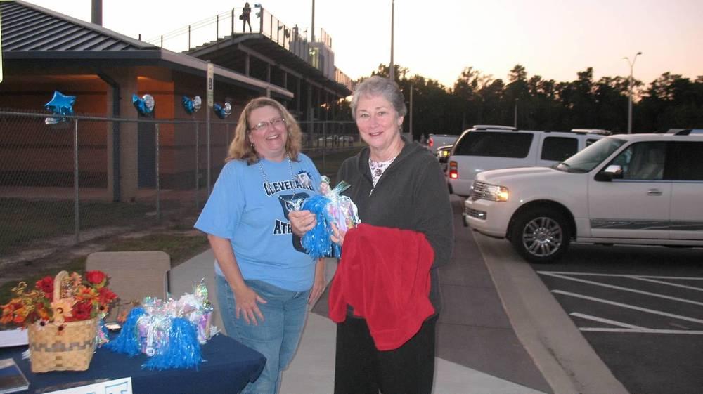 Alumna Carolyn Stevenson receiving Homecoming gifts from Maryann Johnson.JPG