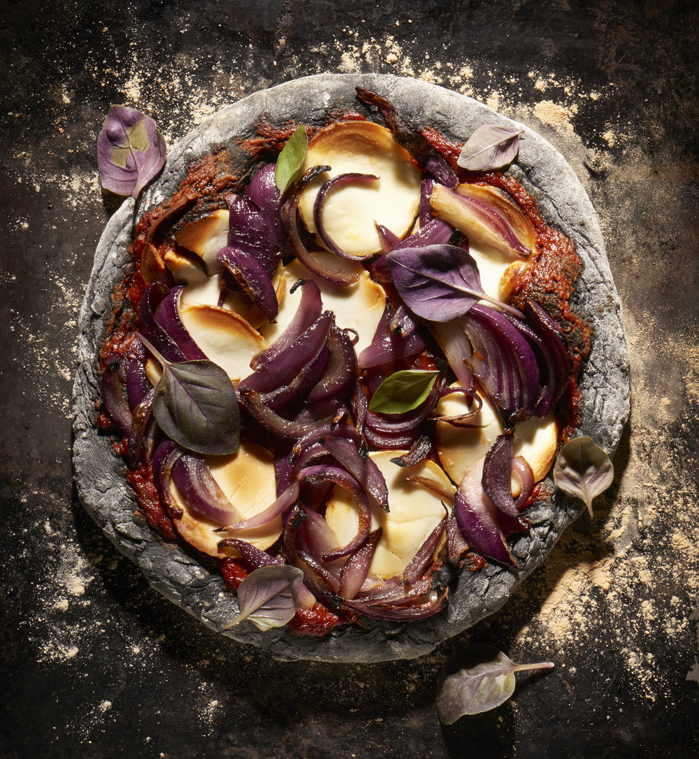 Black pizza with goats cheese and red onions