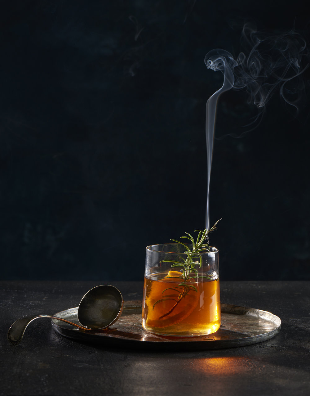 Mulled punch with orange and smoking rosemary garnish. Props styling by Tamsin Weston