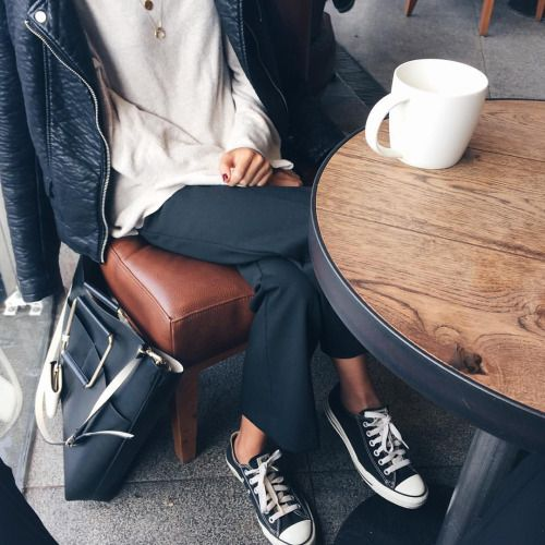 how to wear chuck taylor sneakers, black pants, a cream sweater, black motorcycle jacket and tote