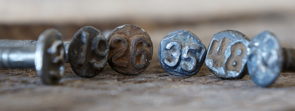 Real date nails recovered by our crews.  The year stamped on the head is the year that rail secion was installed. We drive one in on each peie we create.