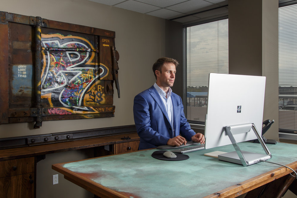 Ryan McGrath at his custom standing desk with copper patina desktop with original graffiti artwork from Rail Yard Studios
