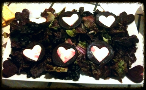 Roasted red beets atop dark green leaf lettuce and fresh mozzarella cheese hearts.