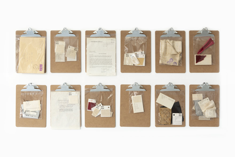 A dozen clipboards hold working documents and correspondence related to the studio's projects.