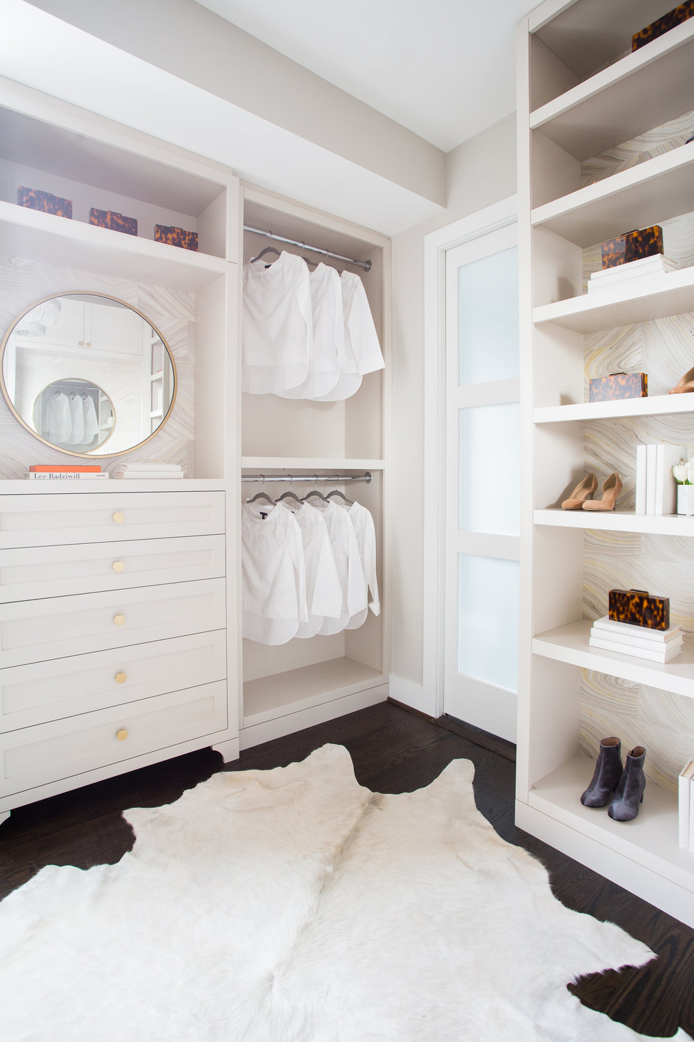 Custom walk-in master closet; birch plywood w/ solid five-piece drawer fronts, wall papered backing, chrome rods
