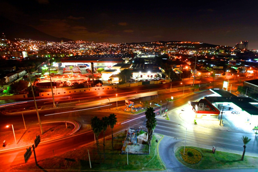 Cars leave streams of light as they rumble around Monterrey at night