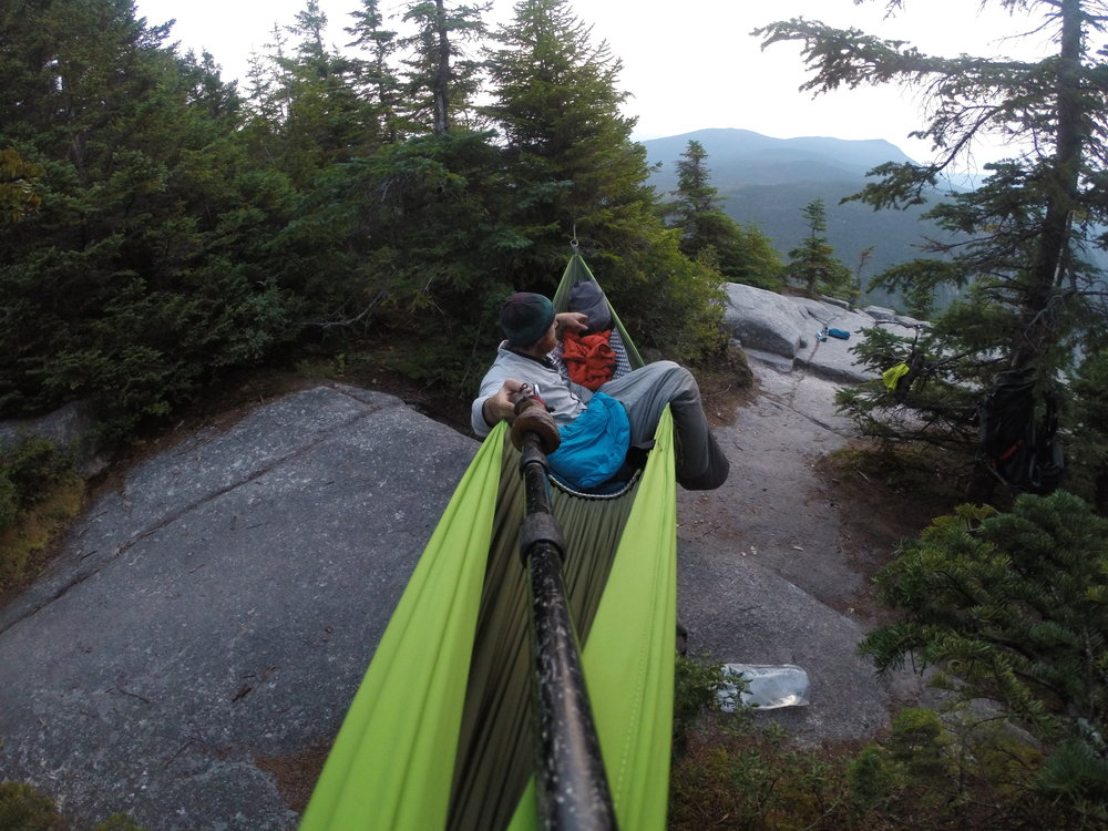 """Chad """"Octo"""" Haynes enjoys sunrise over the Zealand Cliffs in New Hampshire's White Mountains in his Chivey-Green Pares hammock."""