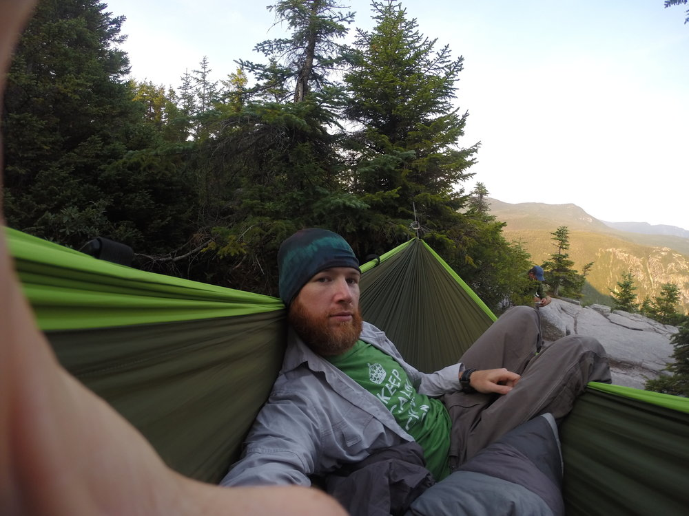 """Chad """"Octo"""" Haynes enjoys sunrise at Zealand Cliffs,New Hampshire in a chivey-green   Pares hammock."""