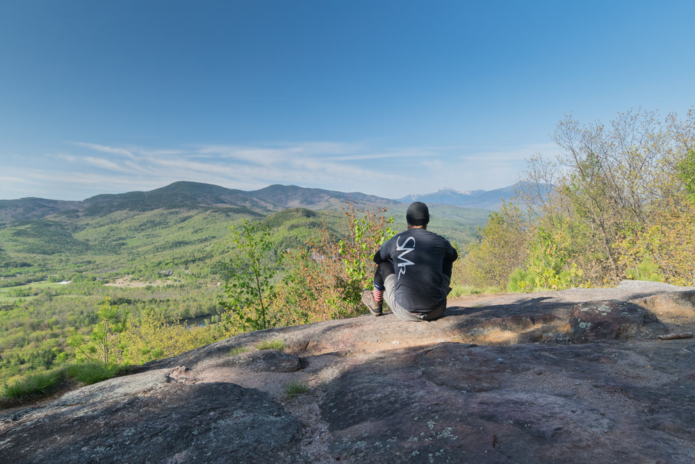 While working at the White Mountains Lodge and Hostel, Erik Barstow spent much of his time exploring nearby sections of the Appalachian Trail. Here he is pictured on Crag Mountain with the Presidential Range in the distance.