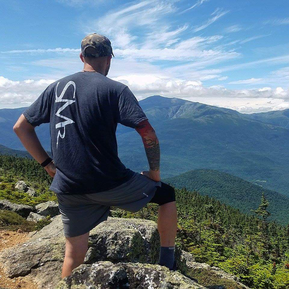 Erik Barstow enjoys the familiar view of the Presidential Range in New Hampshire, on Carter's Dome, along the Appalachian Trail. Photo by D. Nguyen.