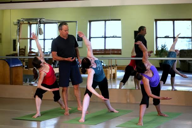 "Coredination yoga students refining their ""Warrior"" pose."