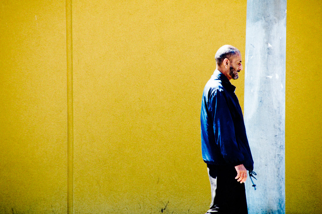 Man with blue jacket on yellow wall.  Montreal.