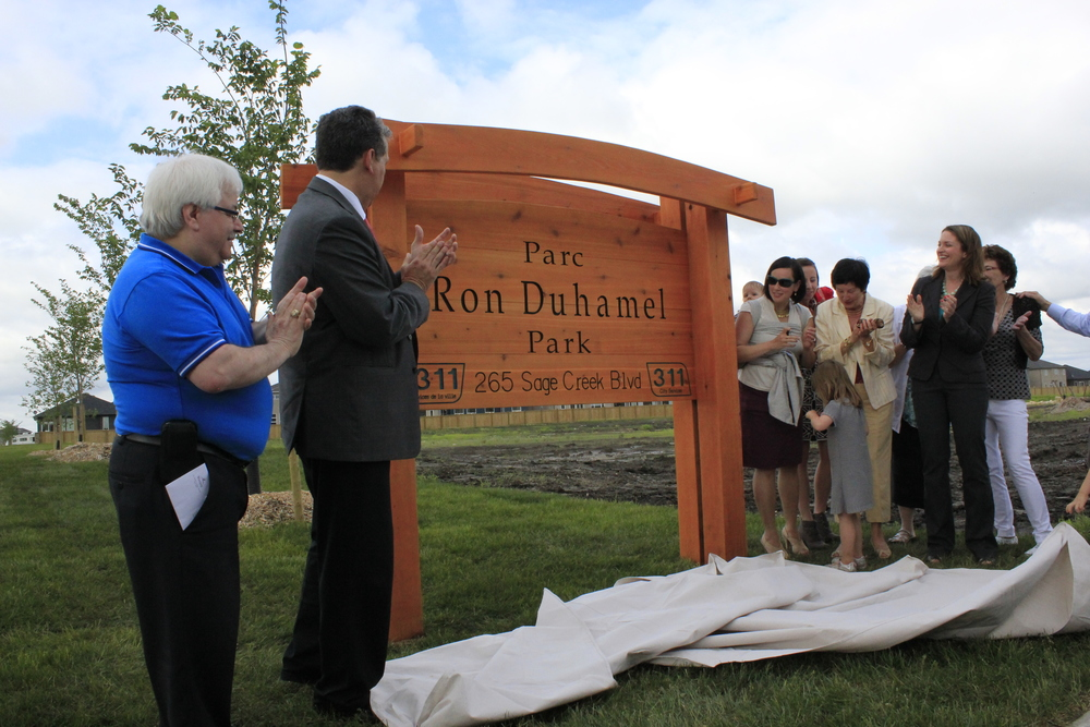 Left to Right - SCRA President Frank Capasso, Councillor Dan Vandal, the Duhamel family, and MLA Erin Selby take part in the unveiling of the Parc Ron Duhamel Park sign.