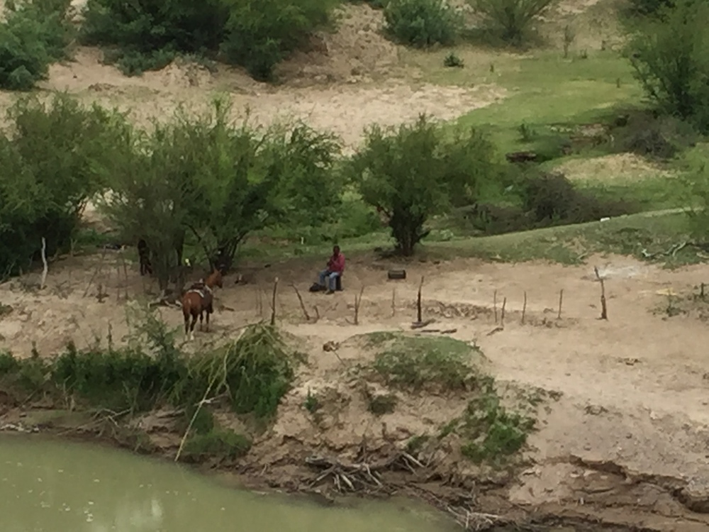 On the Mexican side of the Rio Grande a horseman watches his small group of horses grazing in his corral.