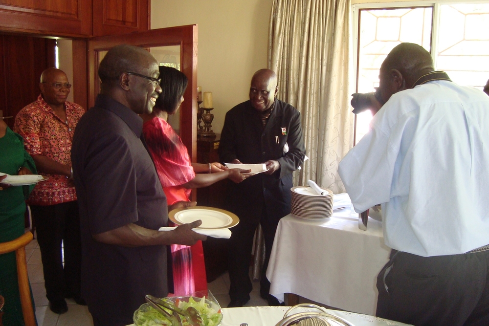 "H.E. President Kenneth Kaunda (in ""Kaunda Suit"") with Alfred Latigo and Mrs. Latigo at a Luncheon after book launch.  GIDE has an office for Southern Africa in Lusaka, Zambia."