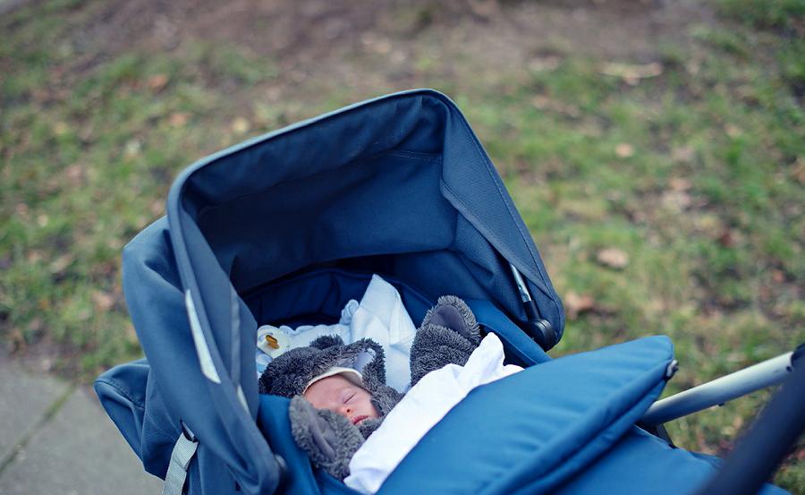 baby-im-bärchen-anzug-im-blauen-kinderwagen.jpg