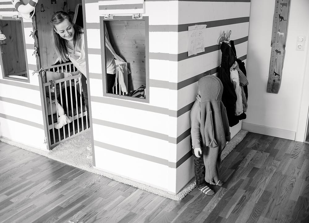 Verstecken spielen mit Mama zu Hause im Wohnzimmer. Na, wo ist er?