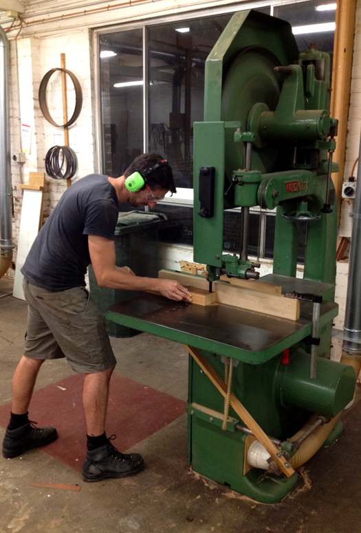 Niall using the bandsaw in the machine room.