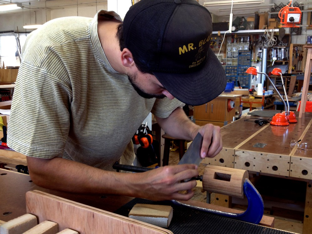 Dominique finishing off the head of his mallet with a cabinet scraper and sanding block.