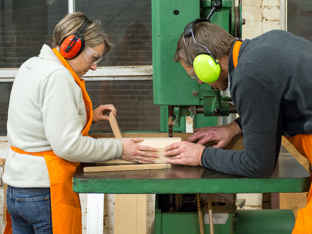 Stephanie and Stuart work together to cut a curved lamination on the bandsaw.