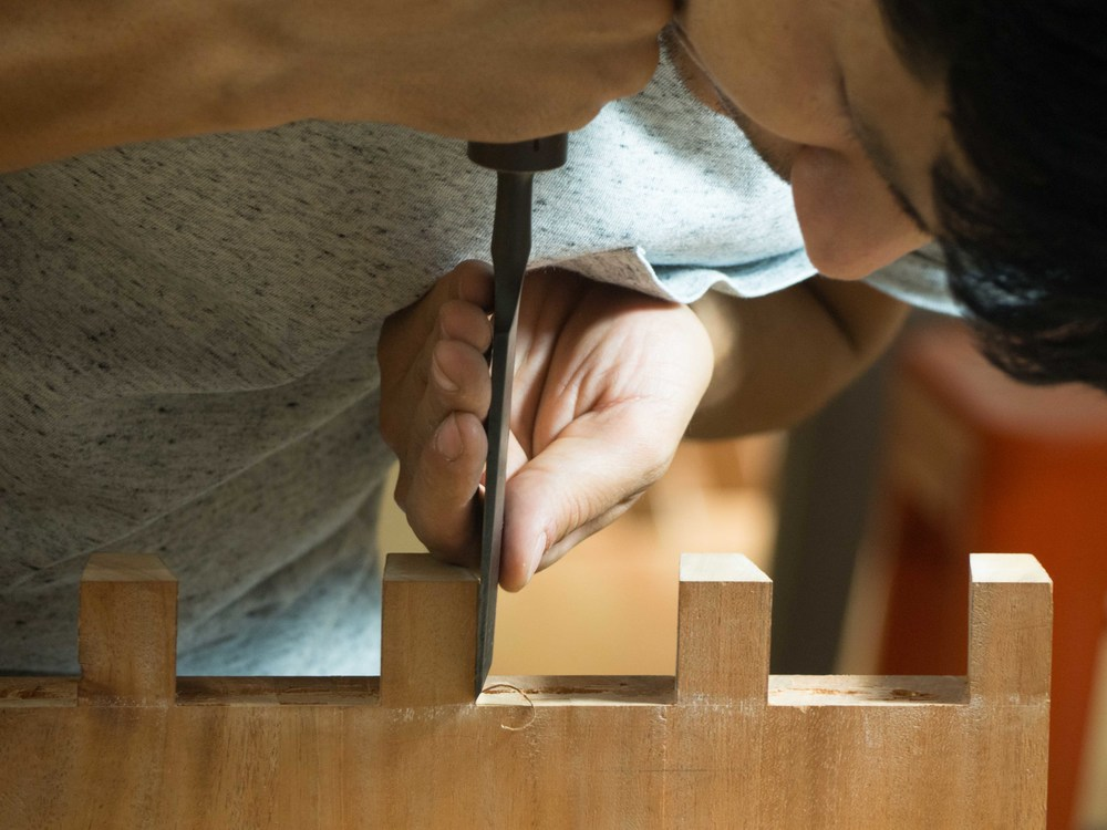 Pouya finely tuning the dovetails for his coffee table project.