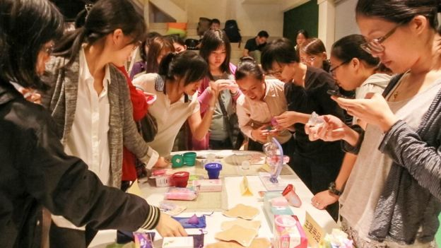 Women look at different menstrual cups with enthusiasm during a promotional event in Taipei (Vanessa Tseng)