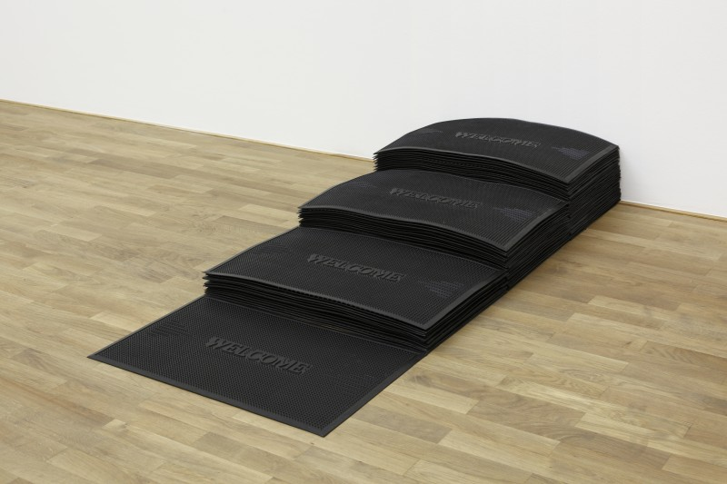 "museumuesum: Felix Gonzalez-Torres Untitled (Welcome), 1991 Rubber mats, photographs, metal, soap, paper. 11 x 29 1/2 in. (27.9 x 74.9 cm).  ""Untitled"" (Welcome) is an astonishing work. It is made of the most common materials, arranged in the most simple forms, but unlike the industrial ready-mades of Duchamp, or the radically geometric sculptures of Judd and LeWitt, it conveys a deeply poignant and profoundly personal charge. It is elegiac, not ironic; intensely felt, not cool and abstract. Made when Felix Gonzalez-Torres faced his own mortality and that of his lover Ross, the artist had no time to waste; he had to make every act and every detail count. And he does. The work is essential in its subject matter and concentrated in its emotion, not just in its form. He compressed into this extraordinary sculpture everything he had learned how to express from the armory of Modern and Contemporary art. It is no accident that as one comes to look at this masterpiece one thinks by turns of the formal simplicity of Judd, the private languages and personal symbolisms of Beuys and Cornell, the desperate yearning of Rothko, and the angry yet bittersweet lyricism of late Picasso raging against death.   The work consists of eighty-some identical black rubber doormats, each emblazoned with the word ""WELCOME,"" which are arranged in four ascending stacks, set with the highest stack against a wall. Unlike his paper stacks, which the viewer is free to take, the doormats are a permanent part of piece. Hidden and interlaced among the mats are everyday items, such as a key, a playing-card, two bars of soap, a papertowel, some scraps of writing, a group of photographs (fig 1). The doormats are public, commonplace, industrial; the items hidden among them are instead relics and traces of personal and shared existence. The soap still gives off its perfume, an aroma that is fading but still lingers like a memory; and all the items similarly evoke treasured experiences that can be recalled, but not recovered, from the past.   The photographs range in character and subject-matter from the sort of pictures of himself (fig 2), family, friends, pets, and loved-ones that nearly everyone has, to images of natural beauty (for example, the sky, a waterfall), as well as pictures of more overtly metaphysical or poetic content, including works by the artist. Susan Sontag has famously remarked: ""Photographs state the innocence, the vulnerability of lives heading toward their own destruction, this link between photography and death haunts all photographs of people"" (Susan Sontag, On Photography, New York 2001, p. 70). Photographs in this sense are expressions of the desire to hold on to and preserve what one cannot bear to lose, but one day will lose anyway.   The haunting combination of innocence and mortality, love and death, is unmistakable in all these pictures. It is especially evident in a photograph of an arm and hand holding a Teddy-bear: an AIDS-induced lesion marks the arm (fig 3). That the Teddy-bear is one of the many toys Felix salvaged from the flea market only increases its poignancy as a totem of childhood vulnerability and love. The ephemerality of beauty and the flickering evanescence of life are also on view in the largest photograph of the group. This depicts the shadow of a man that is cast onto a diaphanous curtain which is caught and illuminated by the light coming from an unseen window (fig 4). In cultures throughout time and around the world, shadows have been used to express the transience of mortal existence. Hence, in the Book of Psalms, for example, one reads, ""Man is like a thing of naught; his time passeth away like a shadow"" (Psalm 144.4), and Pindar, the classical Greek poet, wrote, ""What is a man? Man is but a shadow, the shadow of a shadow. Yet, when beautiful golden light streams from the sky, then bright and brilliant seems his lot"" (Pythian Ode 8). It is striking that Gonzalez-Torres's photographs of the sky, two of which are included here, surely are meant to convey this very sense that beauty is a kind of blessing, although an all too brief and ultimately ungraspable one.   Gonzalez-Torres, of course, is not quoting or referring to the Bible or ancient literature in his art. He does not need to for his meaning to be immediately felt and understood. He found in his impending death a means for understanding, and the urgency to express in direct comprehensible language, the beauty and fragility of mortal existence. He wanted to create something of permanent value, which by being shared with and experienced by the viewers, would continue on after he was gone.   The stacks of doormats that ascend like a series of steps going into a house surely imply the presence of a door. Of course, the threshold, gate or door is a universally understood marker or symbol of the division between two realms of action and being, such as the public and private, the family and the social, the sacred and profane (the word profane literally means outside the gate), the living and the dead. It is easy to imagine these steps, containing the relics of memory and love, as a bridge between the public and private. Indeed, Gonzalez-Torres in his art often straddled these two spheres, with works such as the stacks of candy that were meant simultaneously to be preserved and given away; they are something with an intensely personal significance, and yet also something with a shared, common association of an entirely different order.   Yet the implicit door is surely also the portal between the living and the dead, as in an ancient Roman sarcophagus (marble coffin), where such symbolism was quite common. Beyond this gate lies ""the undiscovered country from whose bourne no traveler returns"" (as Shakespeare described it). One typewritten note hidden among the mats speaks of ""The trip good-bye."" Before leaving the land of the living, on the edge of oblivion, Felix Gonzalez-Torres made a marker, a monument, and blessed it with the traces of love, beauty, and remembrance."