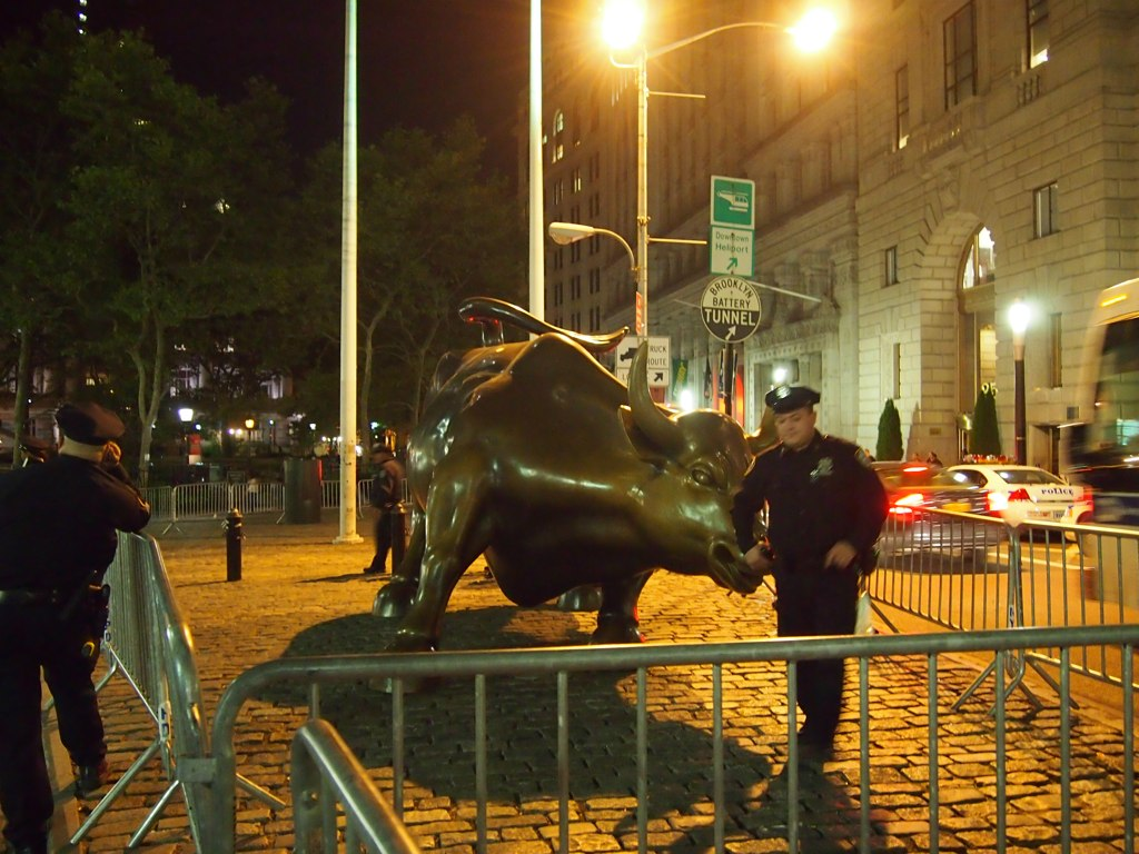 NO MORE BULL… #OWS Last night I acted like a tourist and left the protests Liberty Plaza to visit The Bull. My friend/roommate/writer Dylan Schenker joined me. It was not easy as police had blocked off a lot of the surrounding streets. When we got there, police were guarding the sculpture like an idol. Which, it dawned on me, IT IS. Even if they are doing what they are told, it is still an idol they are protecting, desperately. Aspects of this idol might be totally ok, but, on the whole, it is now a very, very, deeply troubled symbol of the problems we face as a result of its worship. And let me be clear, I do not exonerate myself. I use an iPhone. I have clothes that were made in sweatshops. I often buy the cheapest food despite where and how it was made. Rather I am seeking to raise my own consciousness first, then looking towards how to change my being.  … Moments after this photo was taken, an impromptu march passed by. You can somewhat follow the timeline on the Flickr set.