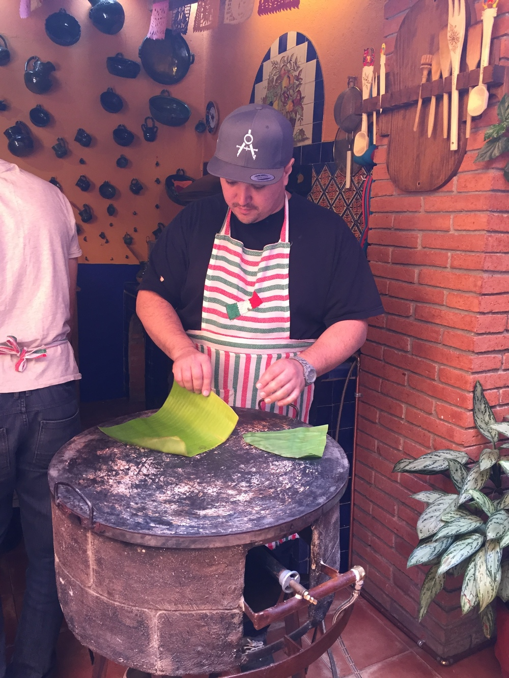 Visiting Professor/ Chef Jason Stanhope  tries his hand at toasting banana leaves for wrapping tamales.