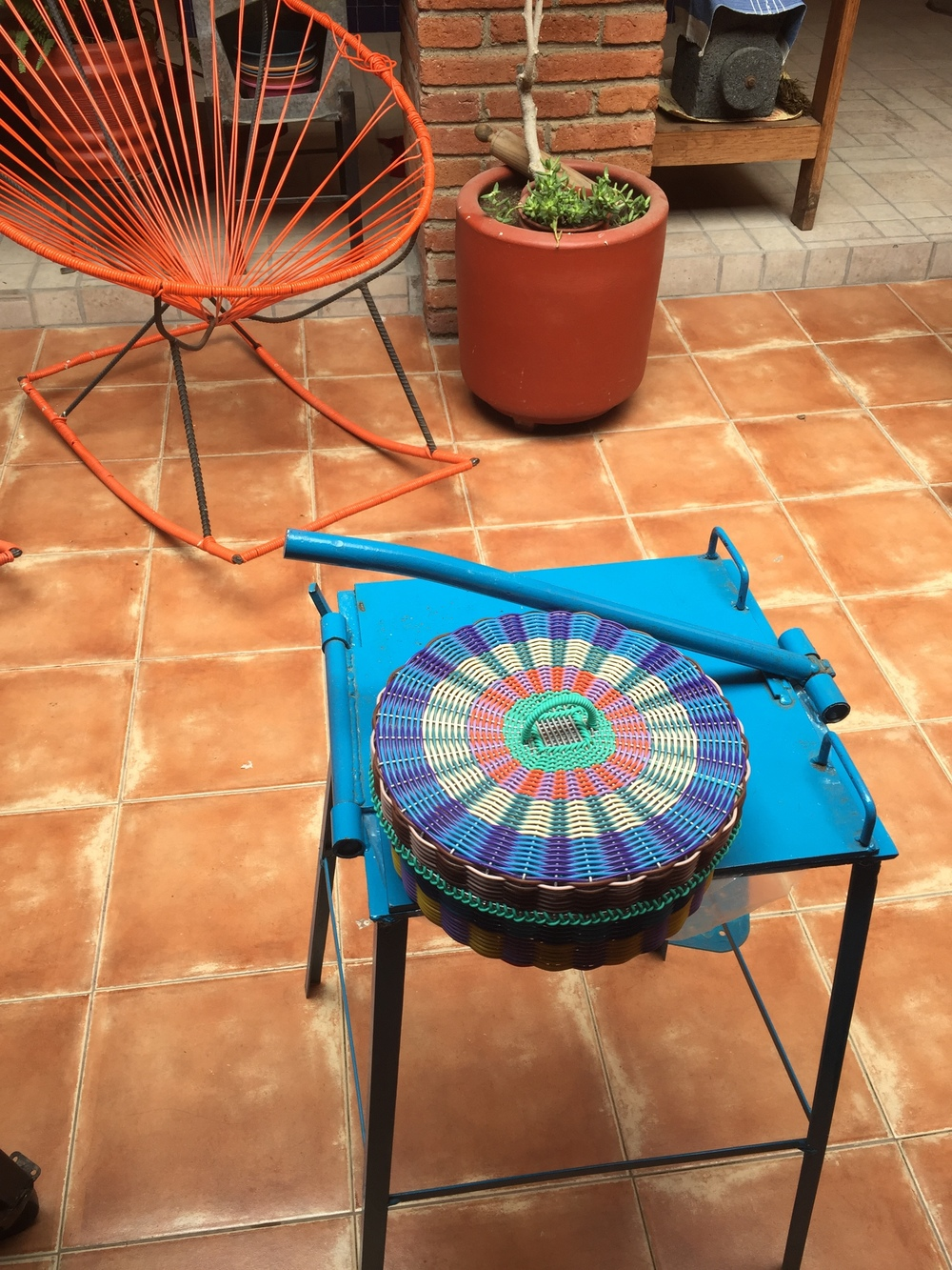 A traditional tortilla press and colorful woven basket for keeping them warm.