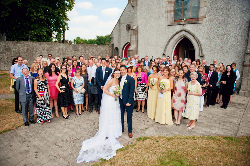Large group shot outside the church. Photography: Weddings by KARA  © - Wedding Location: Kilshane House, Tipperary, Ireland