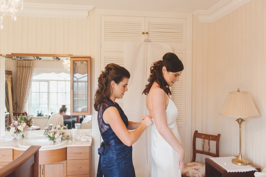 Bride's sister doing up her wedding dress on the morning of the wedding in a cream bedroom