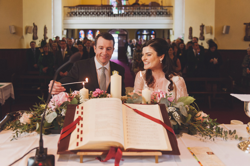 groom and bride lighting candles in the church