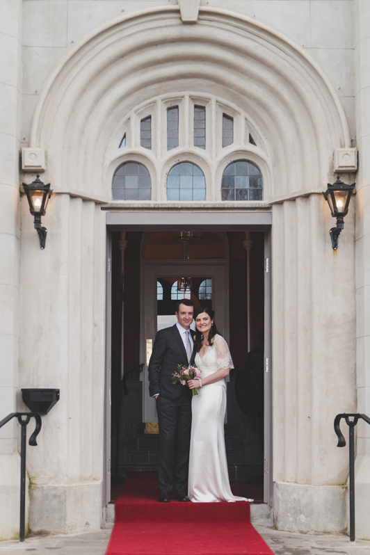 Bride and groom in doorway of bellingham Castle Hotel