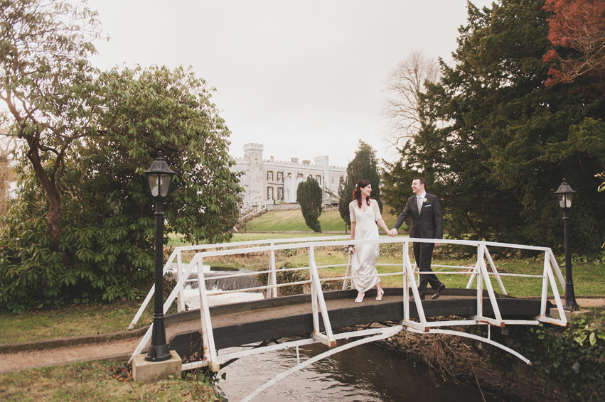 Couple crossing white bridge in Bellingham Castle Hotel Gardens