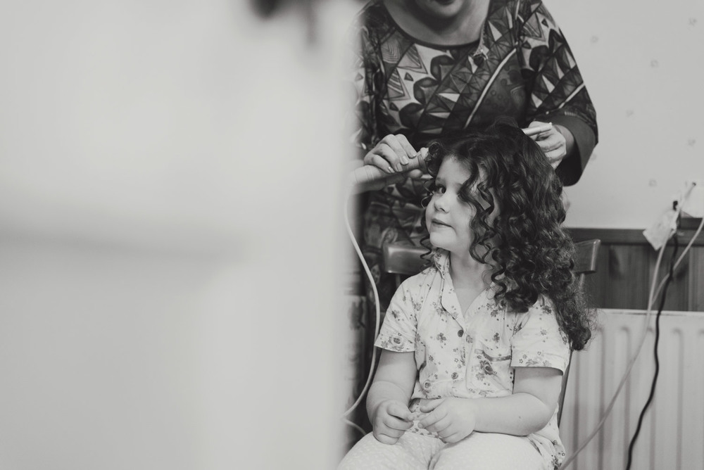 Flower girl on morning of wedding getting her hair done.