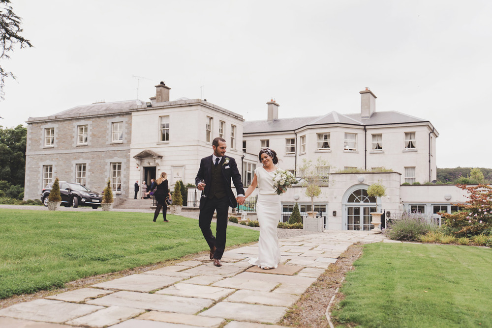 Bride and groom walking in front of Tankardstown House Meath Ireland. Wedding Photography