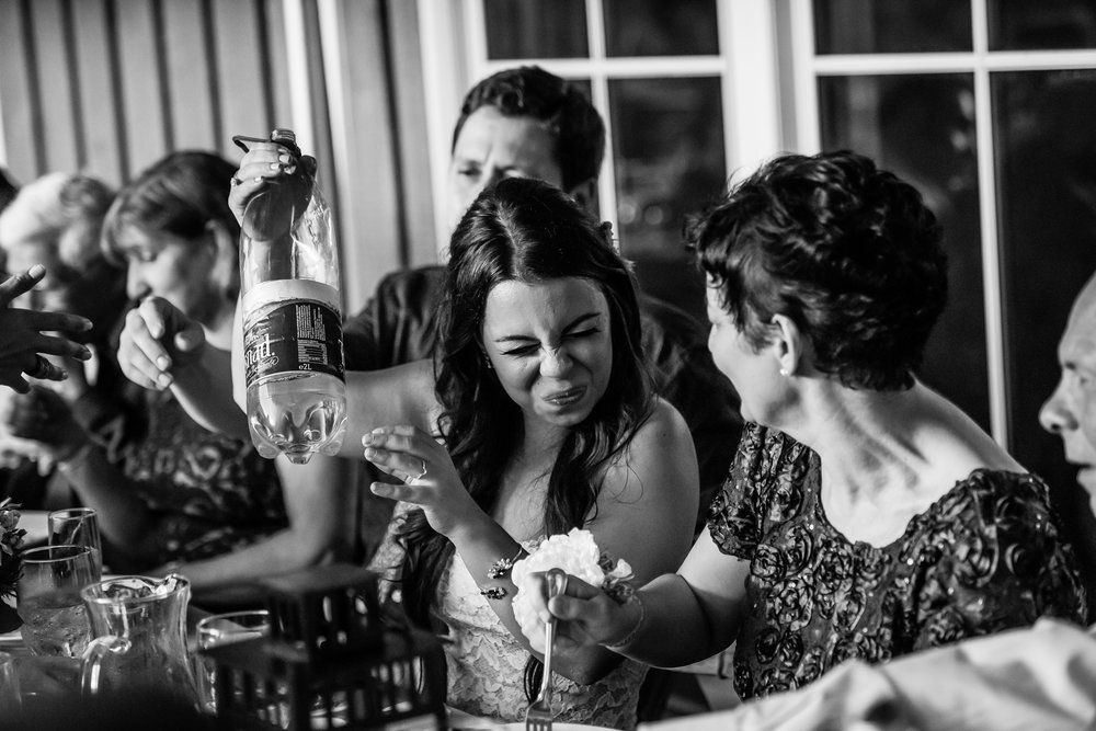 Stefy Hilmer Photography -bride makes face after drinking romanian schnapps during wedding dinner.jpg