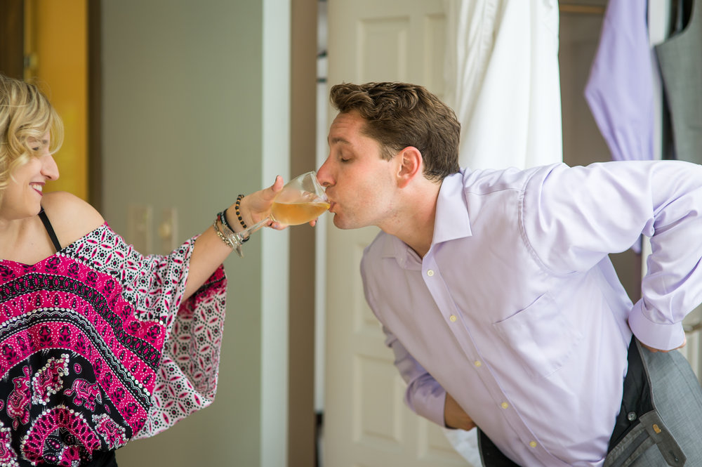 Stefy Hilmer Photography- grooms sister is helping him getting dressed and staying hydrated.jpg