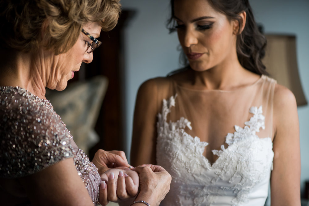 Stefy Hilmer Photography-bride is putting on jewlery for wedding ceremony.jpg