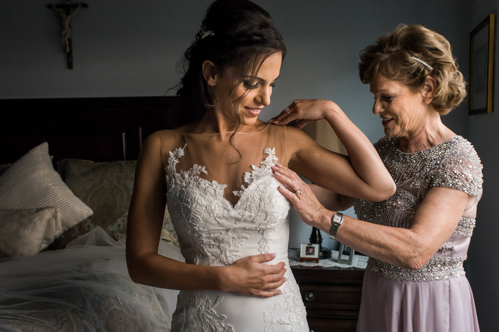 Stefy Hilmer Photography-mom is helping her daugher into her wedding dress.jpg