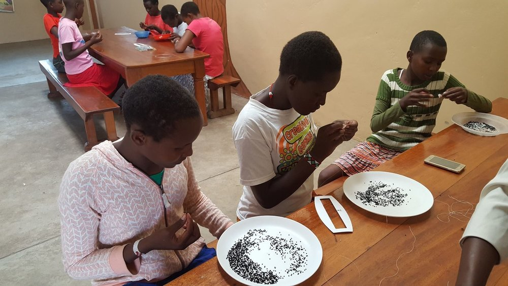 Girls at the Olmalaika Home beading leather for the Jacki Bag